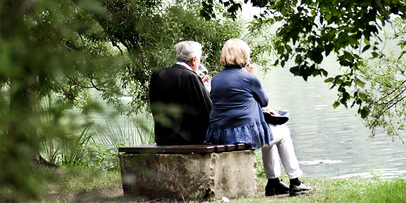 Two elderly people sitting on a bench
